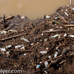 A collection of garbage washed on a bank of the river by a major storm.